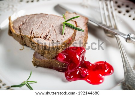 Venison served with cranberry sauce on white plate - stock photo