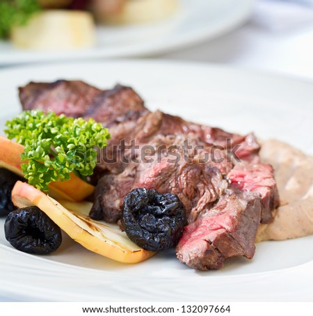 Venison steak cuts on a chestnut puree with dried plums and grilled apple slices - stock photo