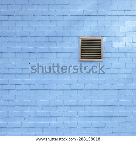 Ventilation grille on the blue brick wall, sun flares - stock photo