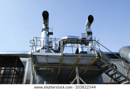 Ventilation pipes of an air condition against blue sky - stock photo
