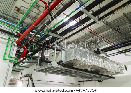 Ventilation system and pipe systems installed on industrial building ceiling. - stock photo