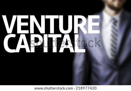Venture Capital written on a board with a business man on background - stock photo
