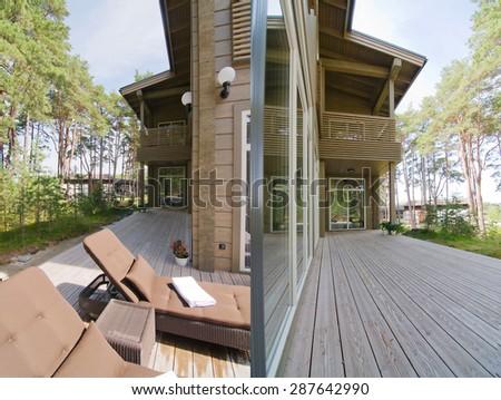 Veranda exterior of a modern wood log house - stock photo
