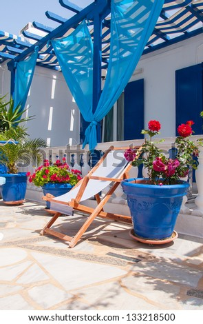 Veranda with pergola and sun beds, surrounded by flowers. - stock photo