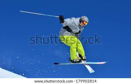 VERBIER, SWITZERLAND - FEBRUARY 24: Freestyle skier performing a tele-heli stunt jump with crossed skis: February 24, 2014 in Verbier, Switzerland - stock photo