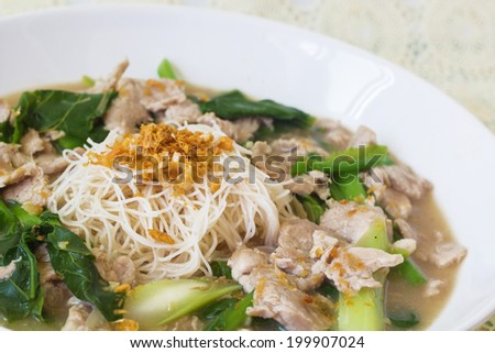 vermicelli noodles topped with pork and kale