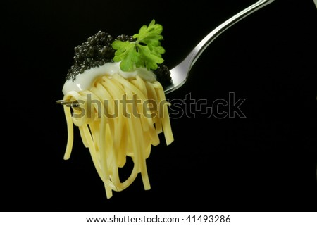 Vermicelli with black caviar on a plug - stock photo