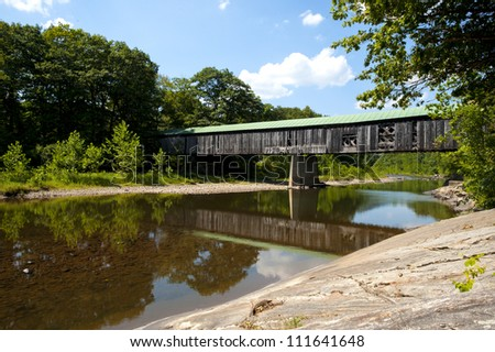 Vermont covered bridge with water. Scott bridge was built in 1870 and is 277 feet long making it one of the longest covered bridges. - stock photo