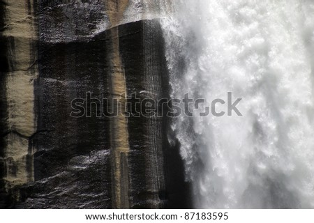 Vernal Falls Detail: Detail of the wet and dry vertical granite rock face alongside the tumbling water of Yosemite National Park's famous Vernal Falls. - stock photo