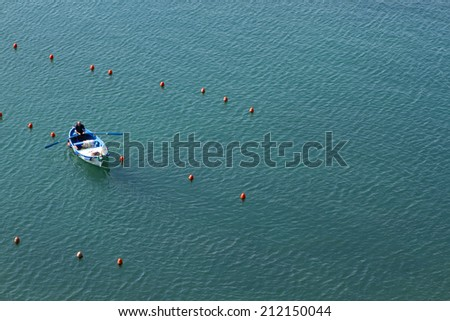 Vernazza, Italy - 7th March 2014: a man on a fishing boat rowing in the blue sea.