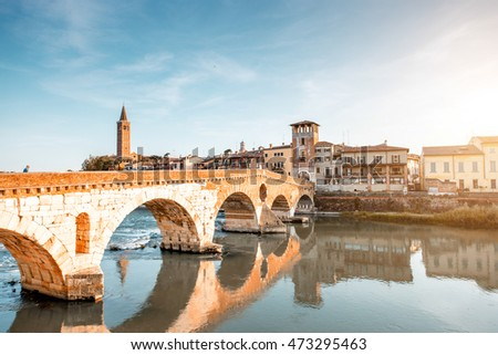 Verona cityscape view on the riverside with historical buildings and towers on the sunset