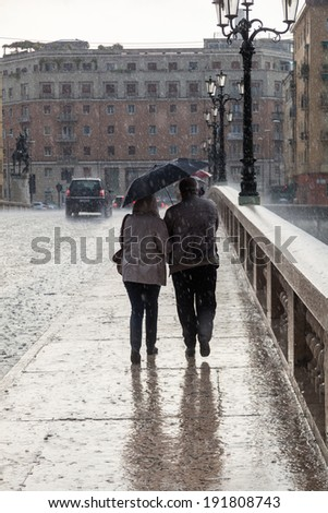 VERONA, ITALY - APRIL 26: unidentified couple on a bridge at heavy rain on April 26, 2014 in Verona. Verona is a popular travel destination and the city is listed under UNESCO world heritage sites.
