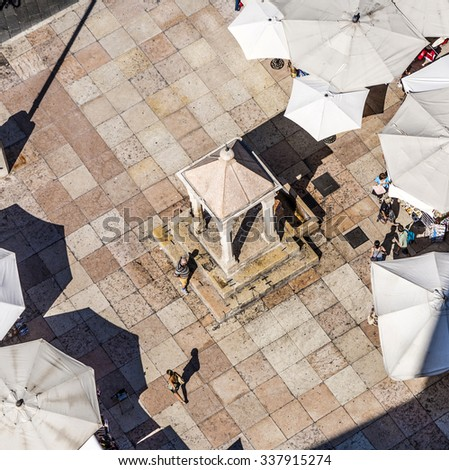 VERONA, ITALY - AUG 5, 2009: aerial view of the Piazza delle Erbe with unidentified people in Verona. The square in the UNESCO protected city was the towns forum in the Roman Empire. - stock photo