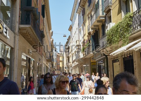 VERONA, ITALY - JULY 11: Busy Via Mazzini with Lamberti Tower in the far background. July 11, 2015 in Verona. Via Mazzini is one of the main commercial streets in Verona. - stock photo
