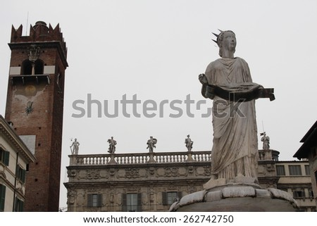VERONA, ITALY - MARCH 17: Madonna Verona fountain at Piazza delle Erbe 13 on March 17, 2015 in Verona. It was built in 1368 by Cansignorio. Background is Palazzo Maffei.