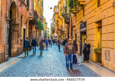VERONA, ITALY, MARCH 19, 2016: people are strolling through a narrow street towards Dominican church of Santa Anastasia in Verona, Italy
