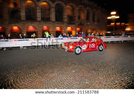 VERONA, ITALY - MAY 15: A red Ermini 1100 Berlinetta drives before the Arena di Verona during the 1000 Miglia classic car race on May 15, 2014 in Verona. This car was built in 1950 - stock photo