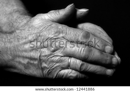 verry old male praying hands with ring in front of black background - stock photo