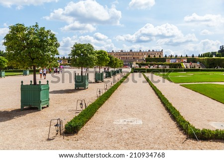 VERSAILLES, FRANCE - AUGUST 05: garden and Palace of Versailles with unidentified people on August 05, 2014 in Versailles. Its one of the largest palace complexes in Europe and its protected by UNESCO