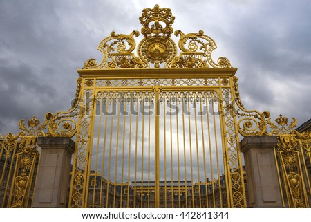 VERSAILLES, FRANCE - JULY 30, 2013: Golden gates to Versailles castle on a cloudy day, June 30, 2013, France. Every day many tourists wish to visit Versailles Palace, It was added to the UNESCO.