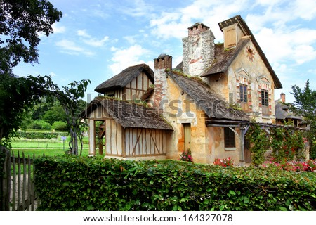 VERSAILLES - JULY 11: Cottage at Marie Antoinette's Little Hamlet, rustic retreat in the park of the Palace of Versailles near the Petit Trianon on July 11, 2010 in Versailles.  - stock photo