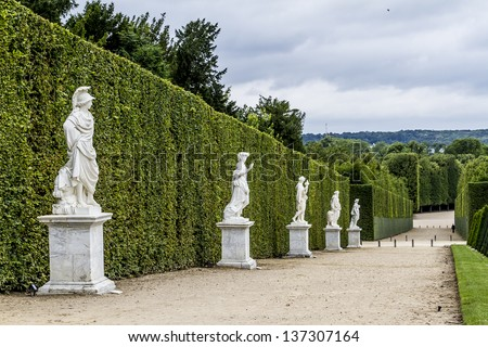VERSAILLES - JULY 12: Sculptures in garden of Versailles Palace, Versailles, France on July 12, 2012. Palace Versailles was a royal chateau. It was added to UNESCO list of World Heritage Sites. - stock photo