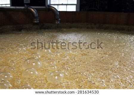 VERSAILLES, KY-MAY, 2015:  Close up of the fermenting tank at Woodford Reserve Distillery.  The bubbles are carbon dioxide and a natural part of the fermentation process.    - stock photo