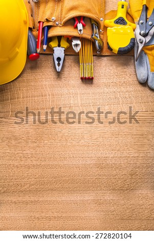 vertical aerial view construction tools  in toolbelt hammer tapeline wrench nippers pliers cutter pencil screwdriver helmet on wooden board  - stock photo