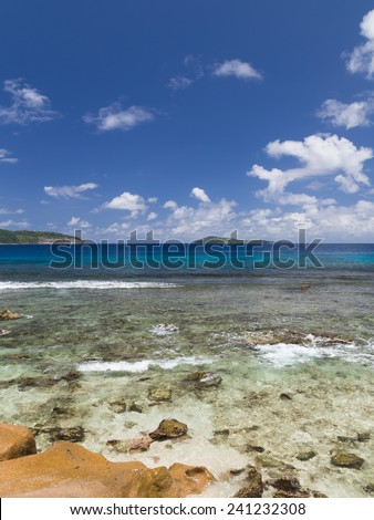 Vertical beautiful seascape with transparent turquoise sea and coast of granite stones, Seychelles