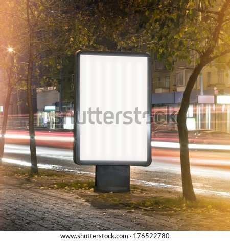 Vertical billboard shot long exposure on a busy evening street. Blank template - stock photo