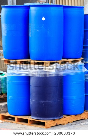 Vertical blue packed barrels on paletts in a chemical plant - stock photo