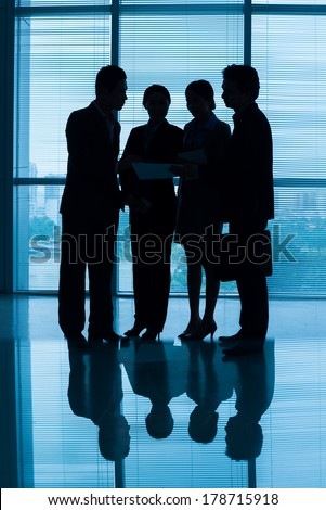 Vertical blurry image of a business team discussing the strategy  - stock photo