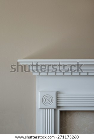 Vertical capture of corner of white mantle and marble trim against beige wall in natural light.  - stock photo