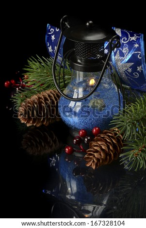 vertical Christmas composition with burning lantern on black background