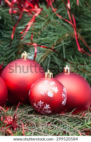 vertical Christmas still life - four red Christmas balls on Xmas tree background - stock photo