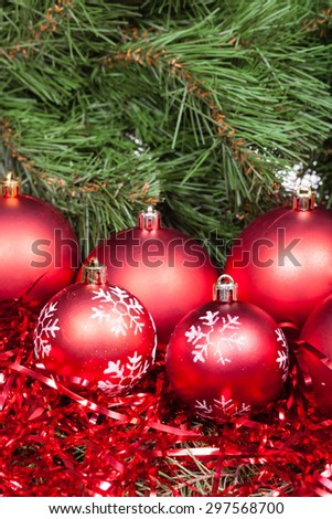 vertical Christmas still life - several red Christmas balls, tinsel on Xmas tree background - stock photo