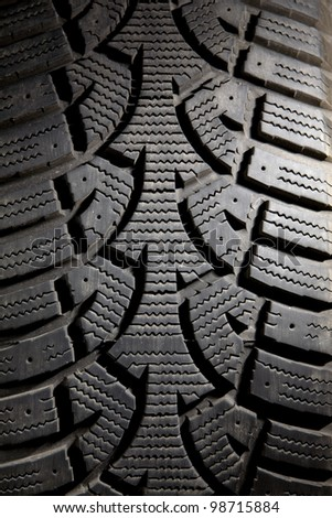 Vertical close up of a dirty snow tire with worn treads. - stock photo