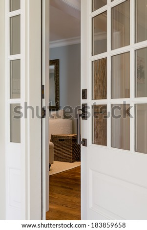 Vertical close-up shot of an open, wooden front door from the exterior of an upscale home with windows.  - stock photo