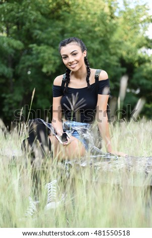 vertical closeup image of a beautiful brunette young woman sitting on a stone, smiling and looking happy, with trees in the background and blurred grass in the foreground