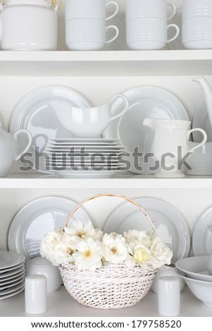 Vertical closeup of a  basket of roses on the shelf of a cupboard full of white plates. Items include, plates, saucers, bowls and a gravy boat.  - stock photo