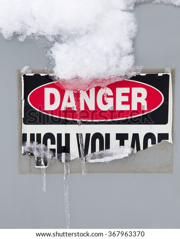 vertical color image of a Danger -High Voltage sticker peeling off, with icicles hanging from it /  High Voltage Peeling Sticker with Icicles - Vertical - stock photo