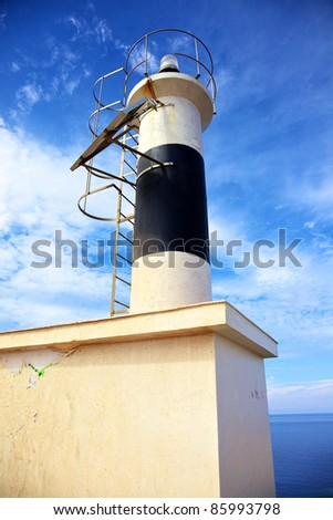 Vertical color image of a small lighthouse on an island in the sea. Summer shot.