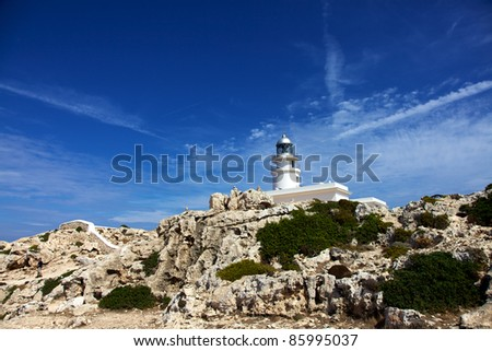 Vertical color image of a white lighthouse in the distance. Rocks and plants in the bottom part of the image and a beautiful blue sky on top. - stock photo