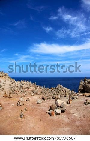Vertical color image of small stones on the coast of an island. Ocean view in a summer day.
