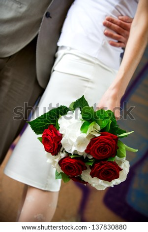 Vertical color wedding image of a groom and bride in short skirt holding flower bouquet of red and white roses.