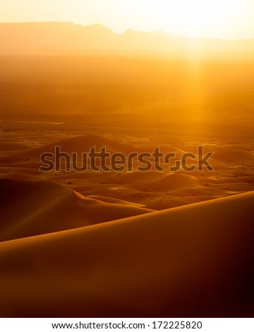Vertical colour image of sunset and speeding car from sand dunes in Erg Chebbi, Morocco - stock photo