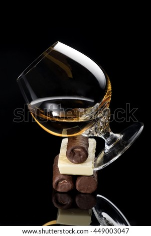 Vertical composition of cognac glass and black and white chocolate on black background with reflection