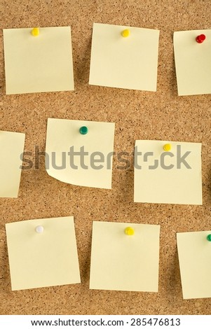 Vertical cork board with many, yellow sticky notes pinned.