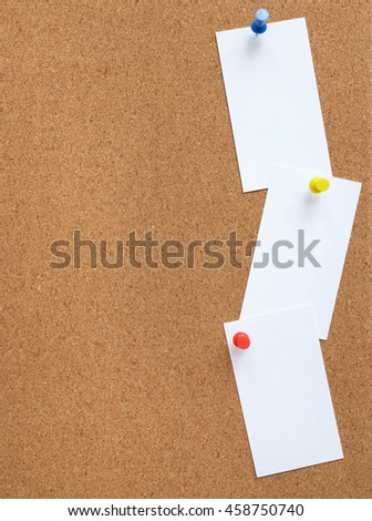 Vertical cork noticeboard with three white cards pinned vertically down the side with coloured drawing pins