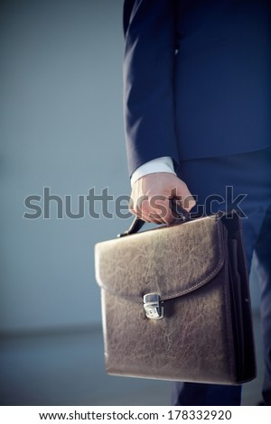 Vertical cropped image of a businessperson carrying a leather briefcase isolated on grey  - stock photo